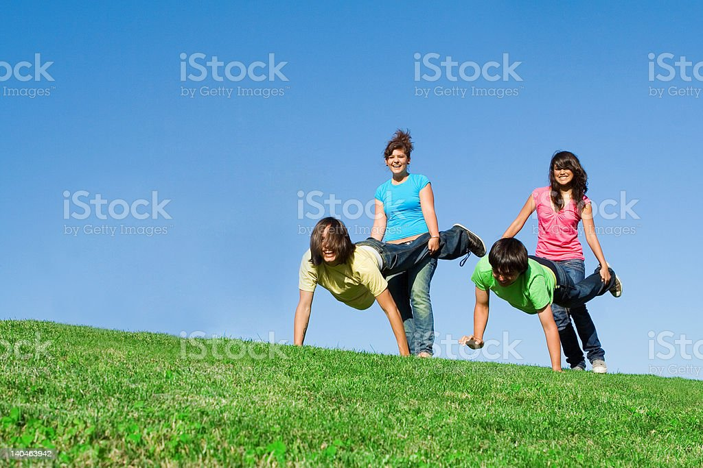 diverse  group of active teens playing outdoors stock photo
