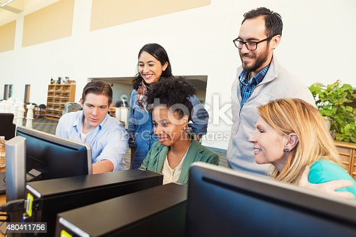 877026364 istock photo Diverse group of adult college students using computer together 480411756