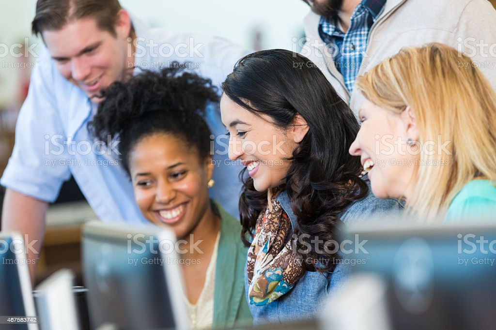 Diverse group of adults continuing education in library computer lab stock photo