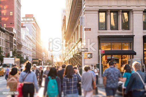 Diverse group of anonymous people walking down busy urban street with bright sunlight shining in the background in New York City