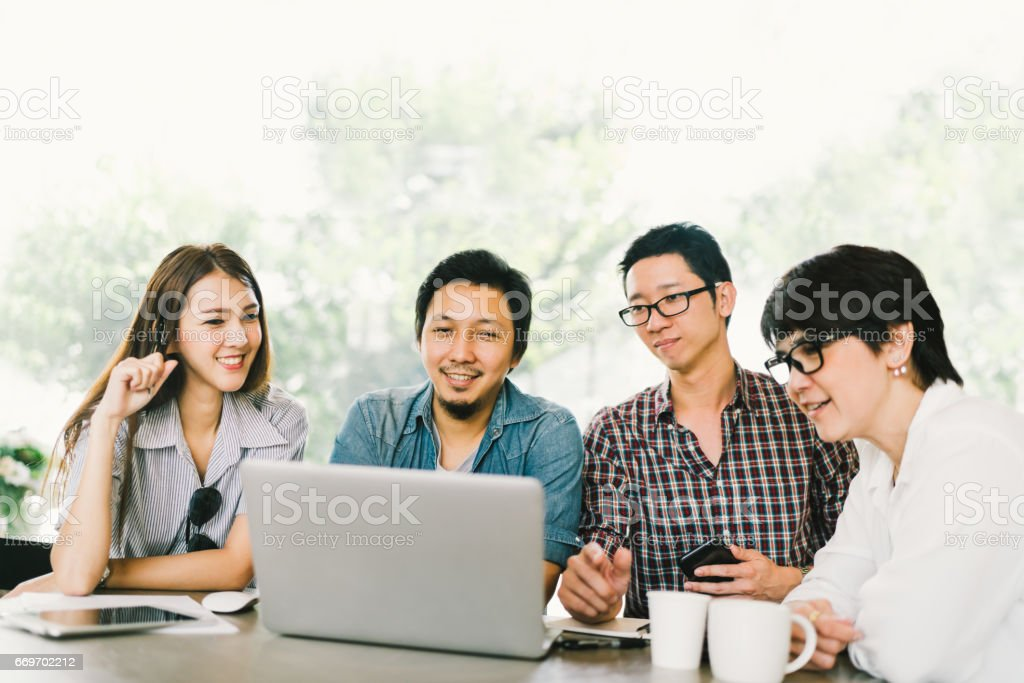 Diverse group of Asian business coworkers or college students using laptop in team casual meeting, startup project discussion or happy teamwork brainstorm concept, at coffee shop or modern office stock photo