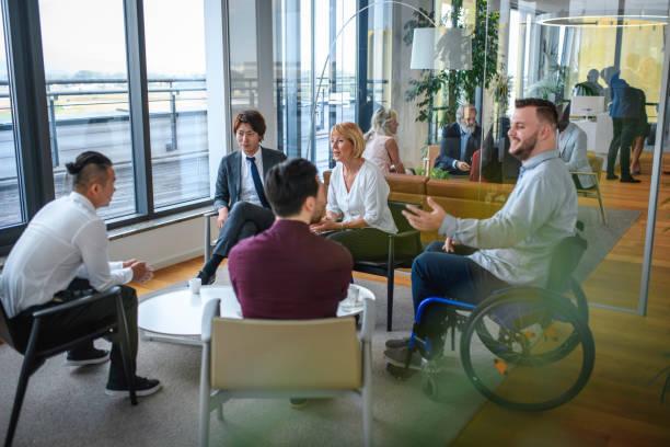 ロビーでの多様なビジネス・アソシエイツ・グループ - disabilitycollection ストックフォトと画像