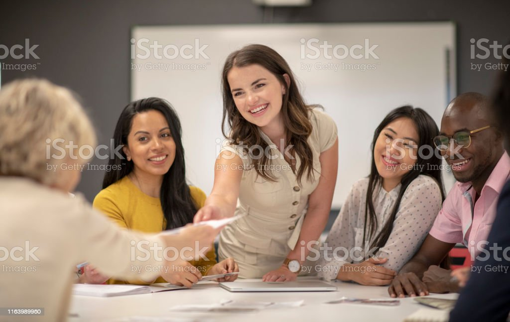 A young caucasian female manager leads a marketing team meeting. She...
