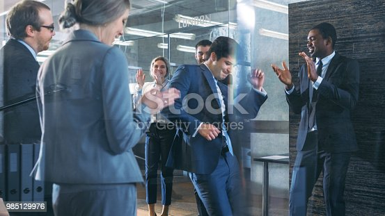 istock Diverse Group of Business People Celebrate Closing of the Deal and Dance. Funny and Friendly Theme. 985129976