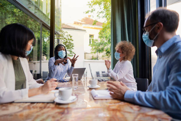 Diverse group of business people having a meeting at the coffee shop while wearing protective masks during coronavirus pandemic stock photo