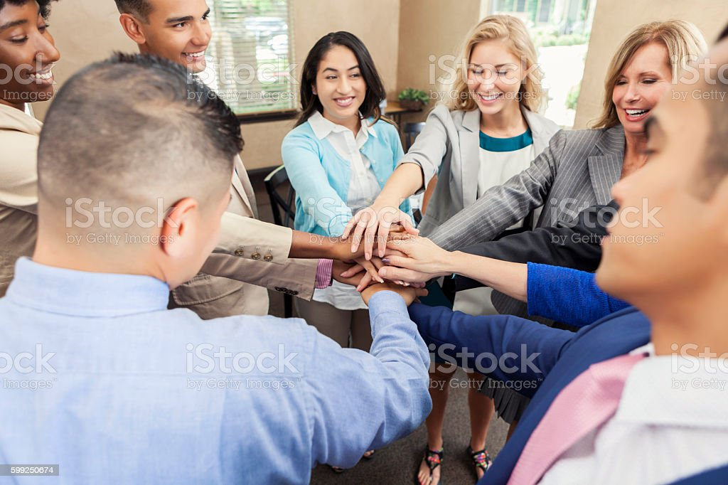 Diverse group of business people put hands together in meeting stock photo