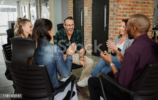 istock Diverse group of business people sitting in circle. Handsome man talking with coworkers in a team building session. 1181423151
