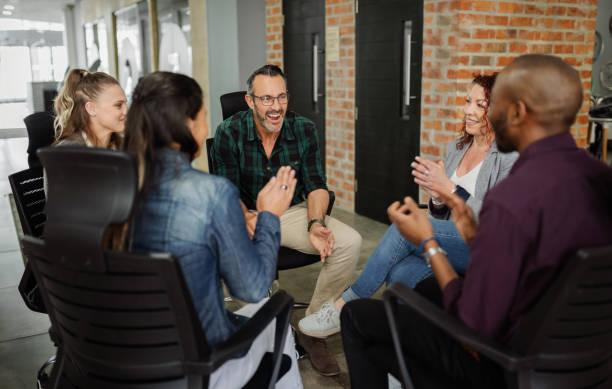 diverso grupo de empresarios sentados en círculo. un hombre guapo hablando con compañeros de trabajo en una sesión de team building. - vestimenta informal fotografías e imágenes de stock