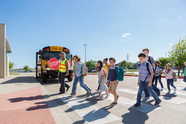 Diverse group of children cross safely to school stock photo