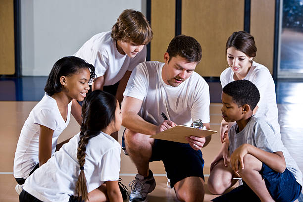 Diverse group of children in gym with coach stock photo