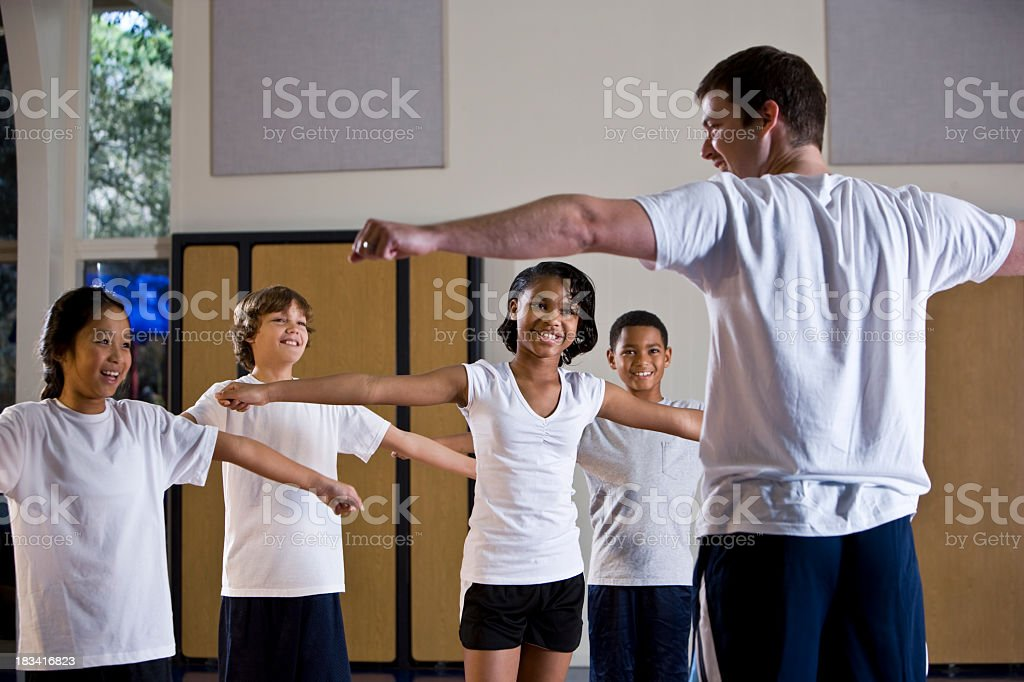 Diverse group of children in gym with physical education teacher stock photo