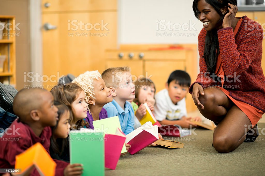 Diverse group of children reading with teacher royalty-free stock photo