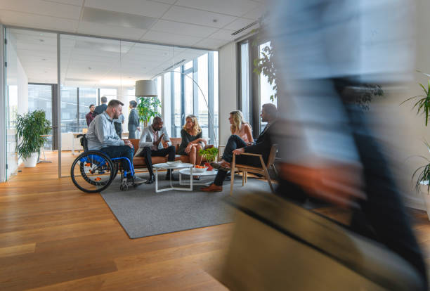 Diverse Group of Colleagues Conversing in Busy Office Lobby Blurred motion of businessman passing with briefcase while diverse group of associates relax and converse in office lobby. persons with disabilities stock pictures, royalty-free photos & images
