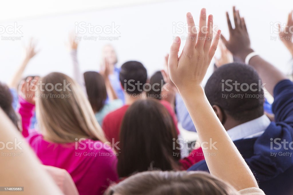 Diverse group of college students raising hands to answer question Diverse group of college students raising hands to answer question Adult Stock Photo