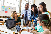 Diverse group of creative professionals discuss ideas in modern office