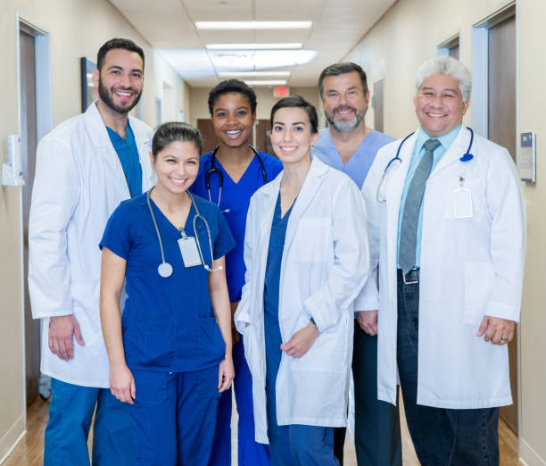 Diverse group of Doctors and Nurses standing in hospital hallway stock photo