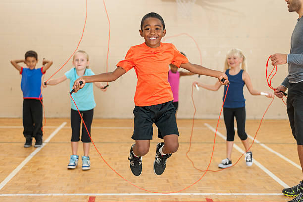 Diverse group of elementary children jumping rope stock photo