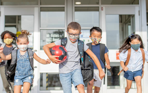 Diverse group of elementary school kids go back to school wearing masks Group of kids return to school during the pandemic. recess stock pictures, royalty-free photos & images