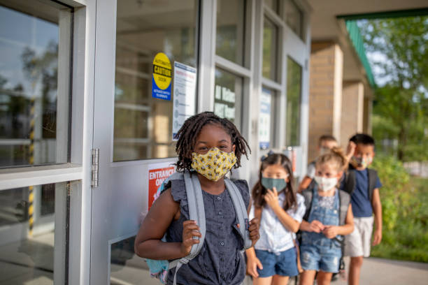 Diverse group of elementary school kids go back to school wearing masks stock photo