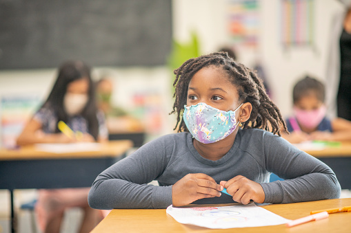 Elementary school classroom wearing masks and social distancing.