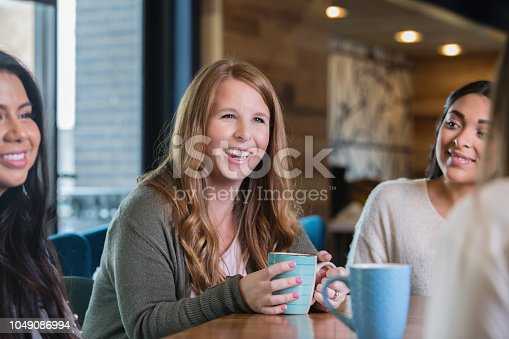 Mid adult Caucasian woman is sitting at table with diverse group of friends. Women are meeting to discuss something and support each other.