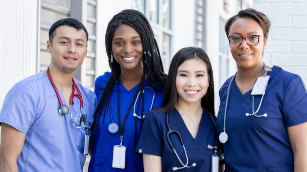 Diverse group of four nursing students standing together outdoors stock photo