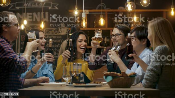 Diverse group of friends celebrate with a toast and clink raised picture id923666724?b=1&k=6&m=923666724&s=612x612&h=i3zxjeeqybsoeq8mrw7 91ut03rc fdj jvozqvpsks=