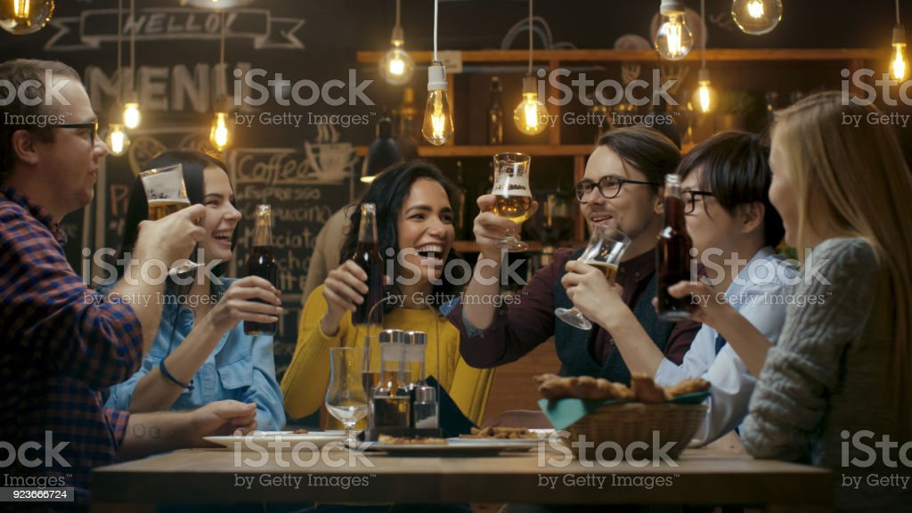 Diverse Group of Friends Celebrate with a Toast and Clink Raised Glasses with Various Drinks in Celebration. Beautiful Young People Have Fun in the Stylish Bar/ Restaurant. - foto stock