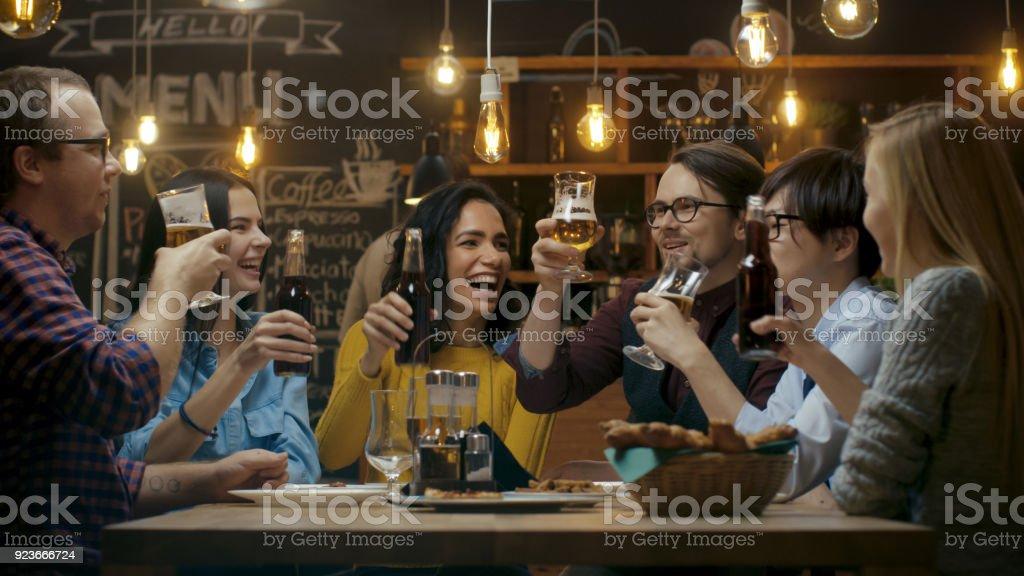 Diverso grupo de amigos celebrar con un brindis y tintineo levantado vasos con diferentes bebidas en la celebración. Hermosos jóvenes dispongan en el elegante Bar / restaurante. - foto de stock