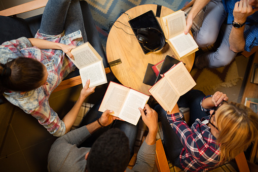 Diverse group of friends discussing a book in library. Directly above.