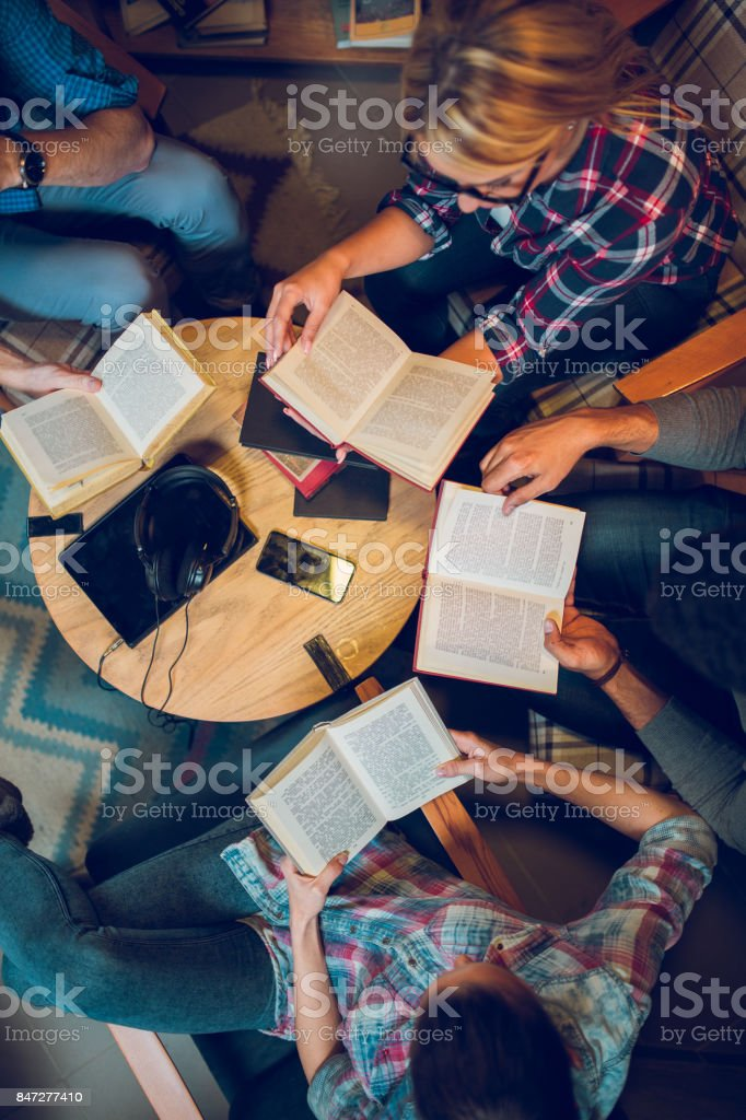 Diverse group of friends discussing a book in library. stock photo