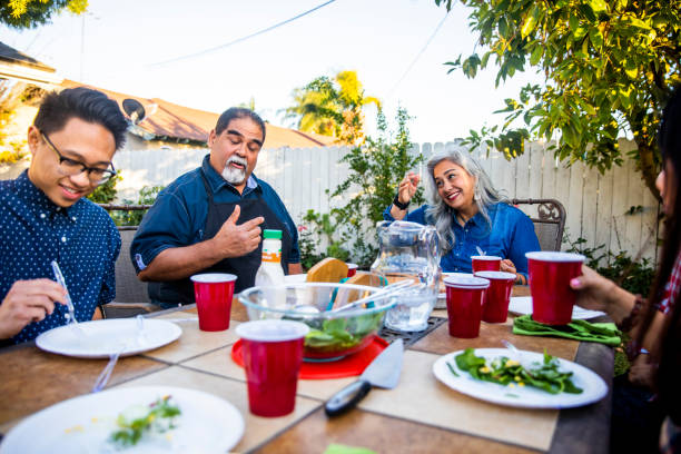 diverse group of friends enjoying dinner outdoors - memorial day weekend stock pictures, royalty-free photos & images