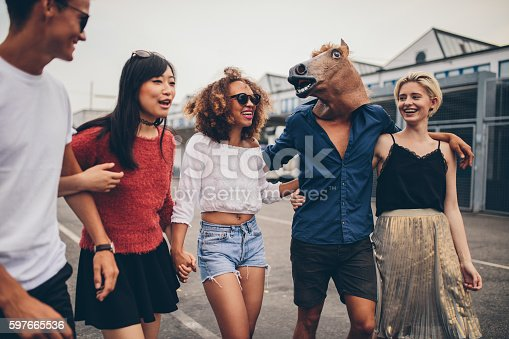 Shot of diverse group of friends having fun together outdoors. Young men and women walking outdoors, with one man wearing horse mask.