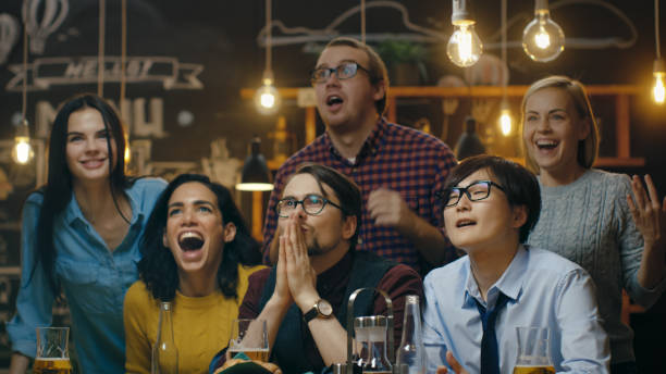 Diverse Group of Friends Watches TV in the Sporstbar. Their Team Scores the Goal and Wins. Young People Cheer. stock photo