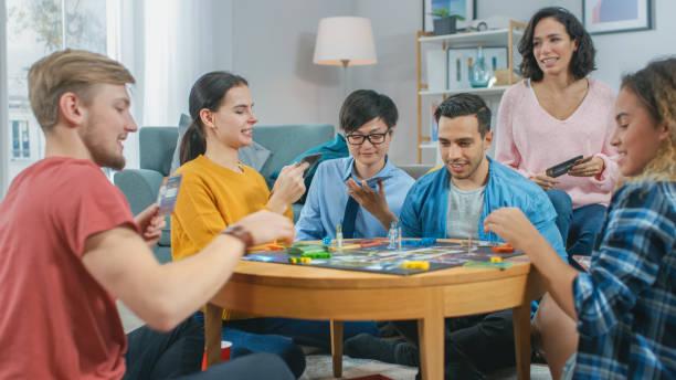 Diverse Gruppe von Jungs und Mädchen spielen in einem strategischen Brettspiel mit Karten und Würfel. Lesekarten und Lachen. Freunde mit Spaß. Gemütliches Wohnzimmer tagsüber – Foto