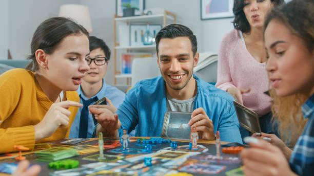 gevarieerde groep jongens en meisjes spelen in een strategisch uniek ontworpen bordspel met kaarten en dobbelstenen. vrienden met leuke lees kaarten, grapjes maken, zetten en lachen in een gezellige woonkamer - vrijetijdsspel stockfoto's en -beelden