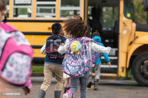 A multi-ethnic group of elementary age children are getting on a school bus. The kids' backs are to the camera. They are running towards the school bus which is parked with its door open. It's a rainy day and the kids are wearing jackets, rain boots and backpacks.