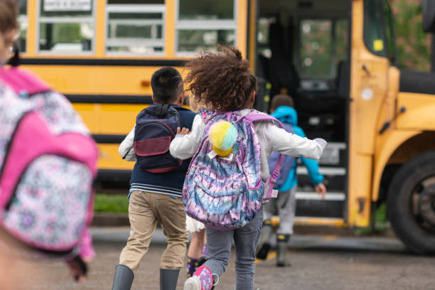 Diverse group of happy children getting on school bus stock photo