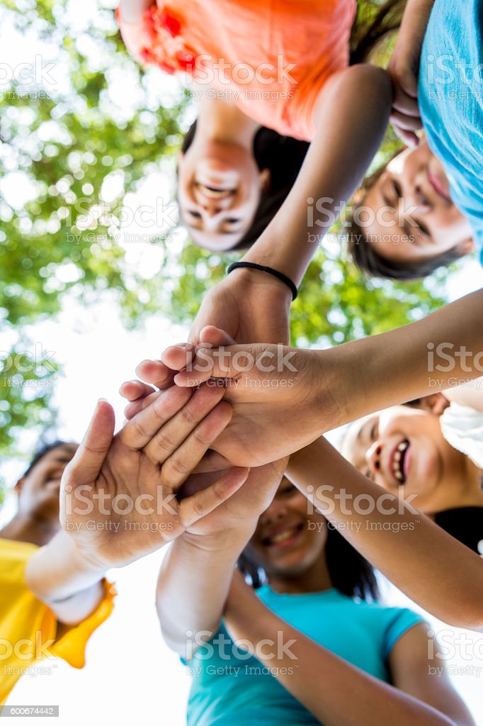 Diverse group of kids outdoors in a huddle stock photo