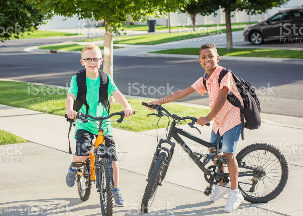 Diverse group of kids riding their bikes to school together stock photo