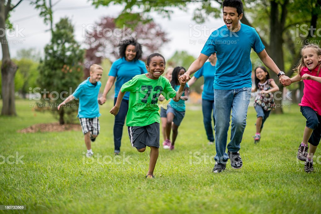 Diverse group of kids running outside at day camp stock photo