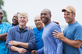 Multi-ethnic group of men standing together, smiling, supporting one another. Mixed ages ranging from 20s to 70s.