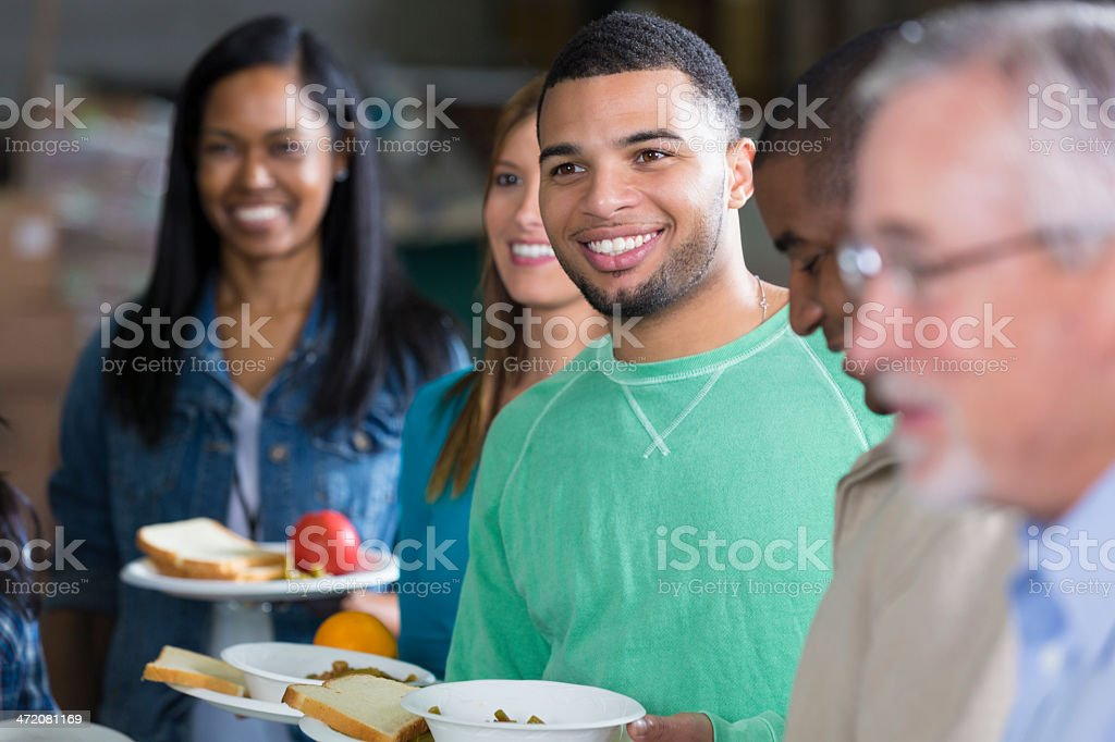 Diverse group of people at community food bank soup kitchen royalty-free stock photo