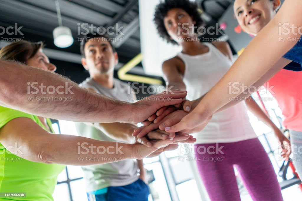Diverse group of people at the gym in a huddle smiling - Lifestyles