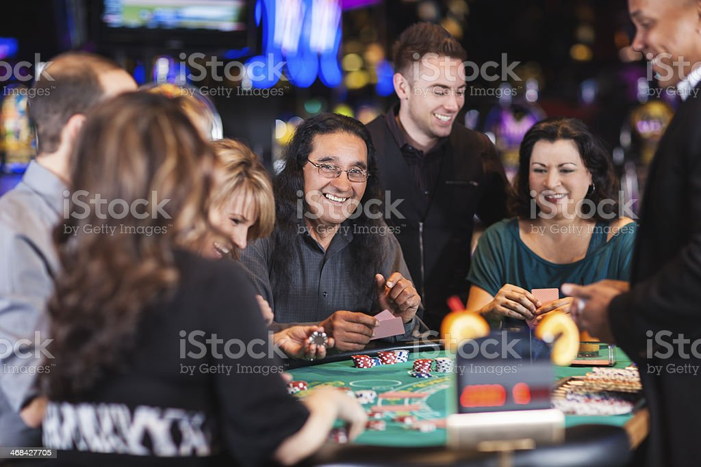 Diverse group of people gambling at casino blackjack table stock photo