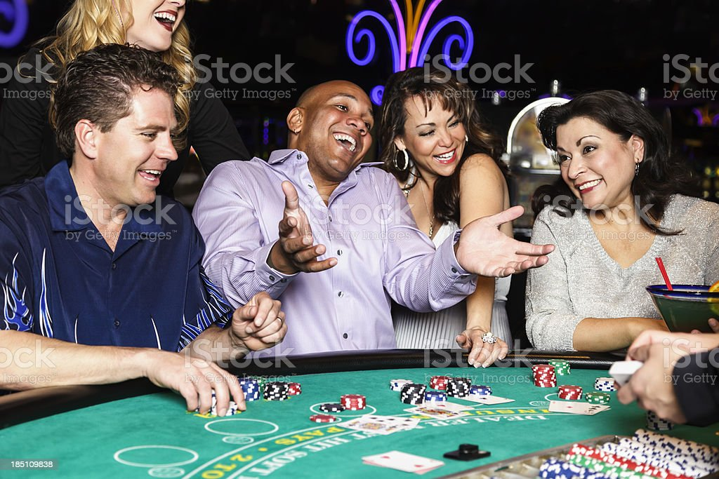 Diverse Group of People Playing Blackjack In a Casino royalty-free stock photo