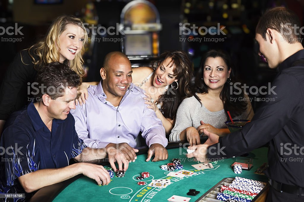 Diverse Group of People Playing Blackjack In a Casino stock photo