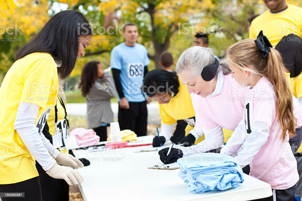 Diverse group of people signing up at charity run/walk event stock photo