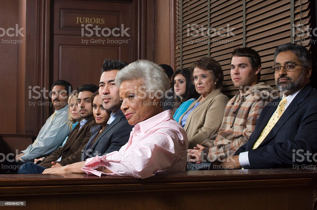 A diverse group of people sitting in a courtroom  stock photo