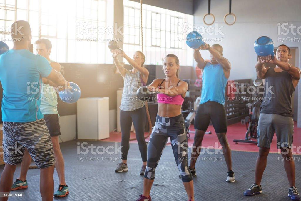 Heterogene Gruppe von Menschen eine Ausbildung mit Wasserkocher Glocken in der Turnhalle – Foto